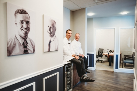 Dr. Baltz and Dr. Rowe sitting on the in-office coffee bar at Highpoint Dental Care