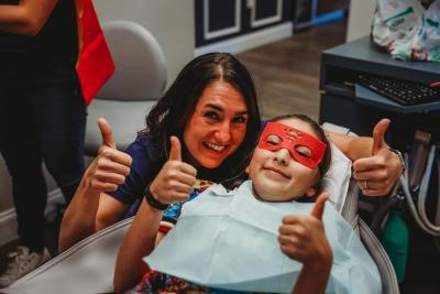 Dental Hygienist with child patient dressed as superhero